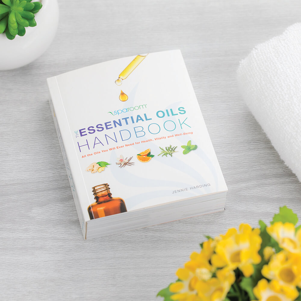 Essential Oil Handbook On Table with Flowers
