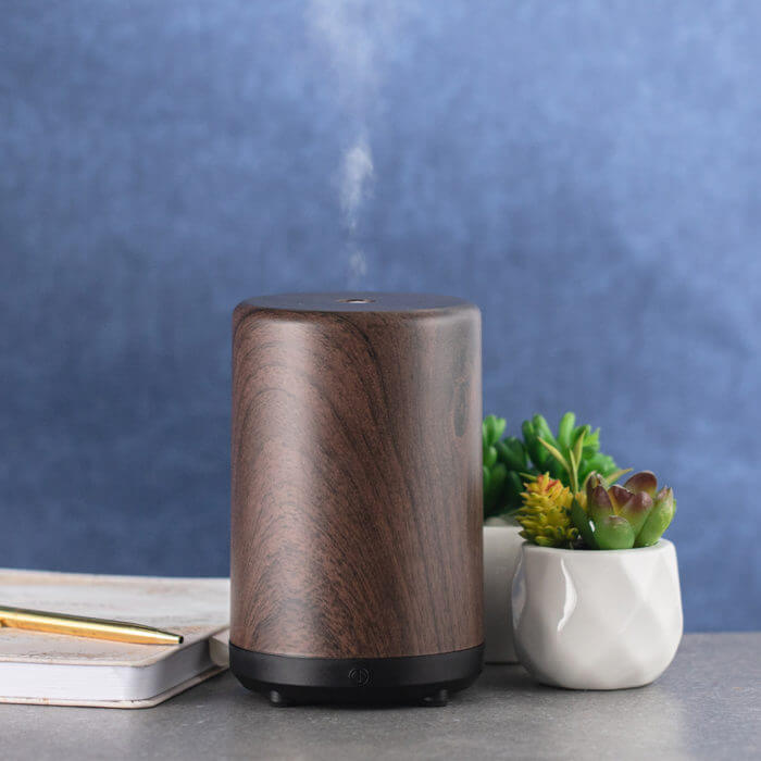 HerbalAir 2.0 woodgrain diffuser on table with plants and notebook